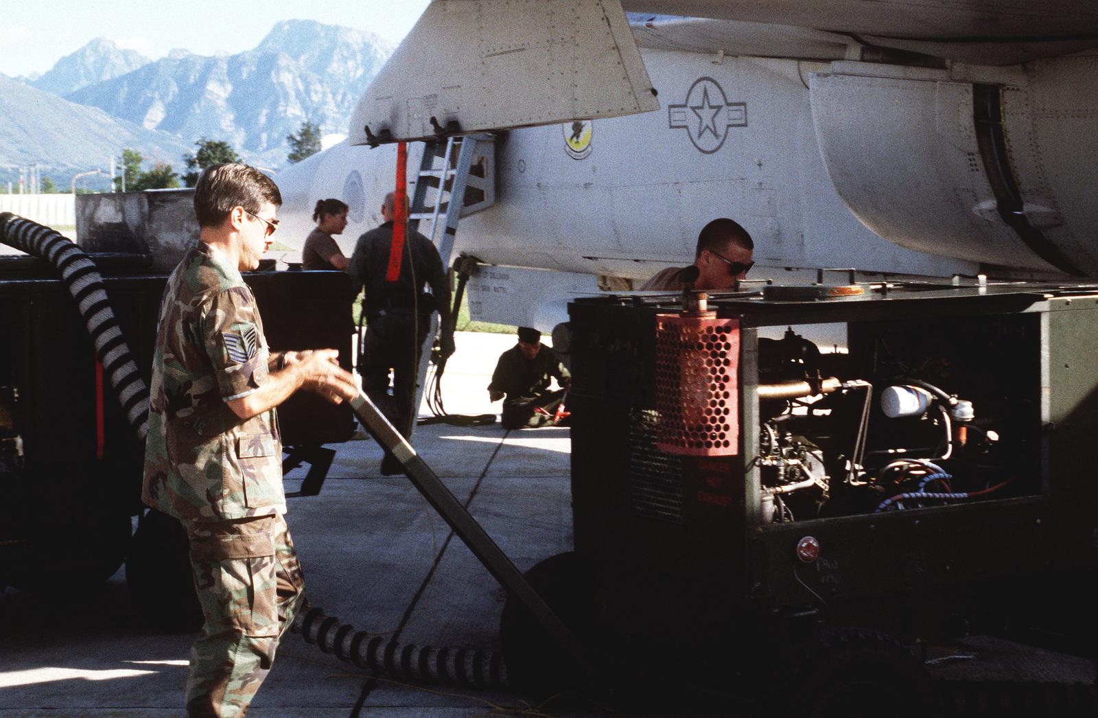 MASTER SGT. Reeves (left), the production supervisor for the 429th Electronic Combat Squadron, 27th Fighter Wing, Cannon Air Force Base, NM, helps position support equipment near an EF-111A Raven aircraft on the flightline. The ground crew is preparing the aircraft for a NATO airstrike against the Bosnian Serbs
