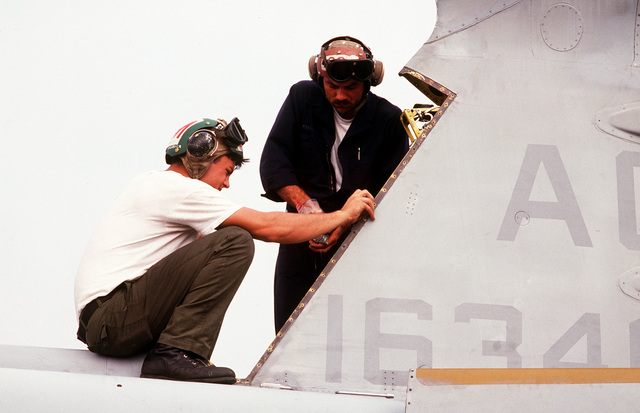 Two US Navy aircraft maintenance personnel perform a 56 day preventive maintenance inspection on a US Navy EA-6B Prowler on the flightline. The aircraft is from Tactical Electronic Warfare Squadron 141 deployed on board the aircraft carrier USS THEODORE ROOSEVELT (CVN-71). The ROOSEVELT is operating in the Adriatic Sea in support of the operation