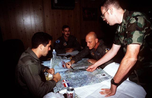 US Air Force EF-111A Raven pilots from the 429th Electronic Combat Squadron, 27th Fighter Wing, Cannon Air Force Base, NM, receive an intelligence brief from 1ST LT. Cahill (right), prior to NATO airstrikes against the Bosnian Serbs