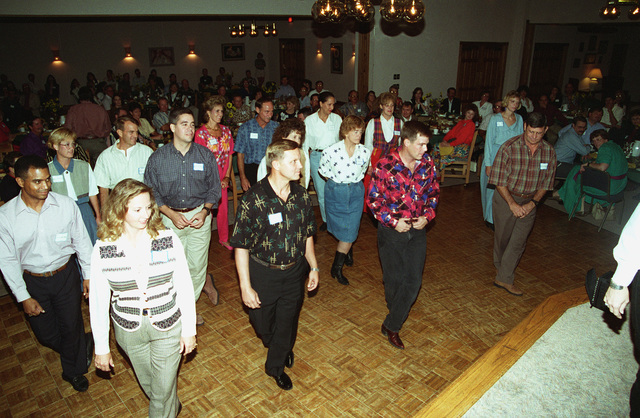 Secretary of the Air Force, Dr. Sheila Widnall and the commander of the 27th Fighter Wing, Brig. GEN. Mike Guth, along with other guests do a line dance at the Officer's Club