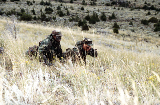 Crouched down at the edge of an open field that they will have to sprint across, SENIOR AIRMAN Michael O'Quinn, 341st Operations Squadron, points out to AIRMAN Bruce Howard Clark, Jr., 341st OSS, a clump of shrubs that they will use as cover to avoid being seen by enemy snipers