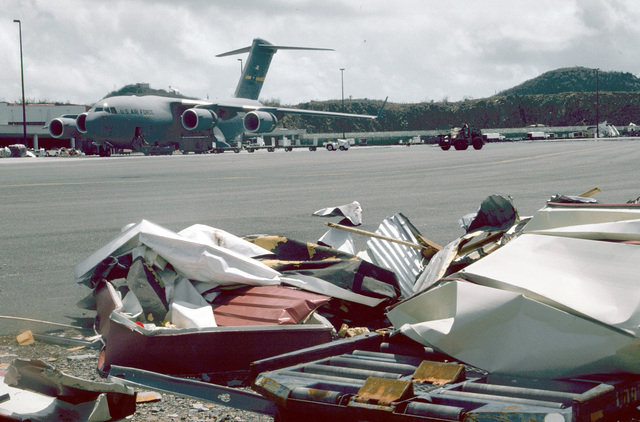 Beyond the debris along the runway, cargo was unloaded off the C-17 at Cyril E. King Airport on St. Thomas. The relief efforts began after Hurricane Marilyn hit the Virgin Islands on 15 September 1995