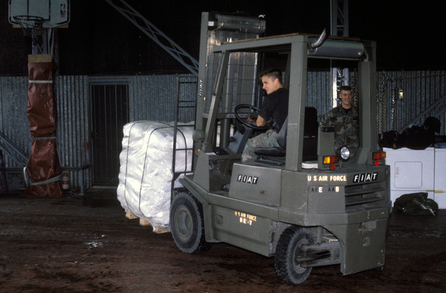 A U.S. Air Force forklift driver with the 37th Airlift Squadron, Ramstein Air Base, Germany, moves pallets of sacks of wheat flour in preparation for loading onto a U.S. Air Force C-130 Hercules aircraft which will fly into Sarajevo, Bosnia-Herzegovina on a relief mission. The C-130 crews fly two missions a day into the Sarajevo airport dropping off approximately 30 metric tons of wheat flour to the besieged residents. For recreation, the personnel have set up a basketball hoop