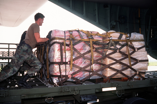 U.S. Air Force personnel with the 37th Airlift Squadron, Ramstein Air Base, Germany, push pallets of relief supplies into a U.S. Air Force C-130 Hercules aircraft which will fly the supplies into Sarajevo, Bosnia-Herzegovina. The three-year-old relief effort has been able to resume their relief mission after a five month hold due to aircraft receiving ground fire over Sarajevo