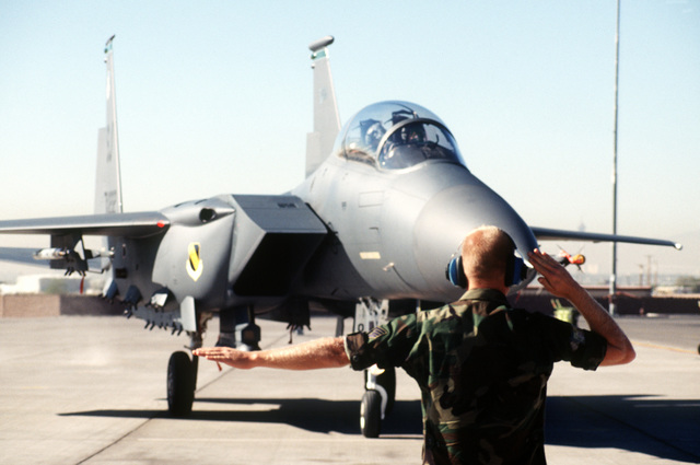 A crew chief marshals out an F-15E Eagle from the 4th Fighter Wing, Seymour Johnson Air Force Base, North Carolina, during GUNSMOKE 95 competition. Exact Date Shot Unknown