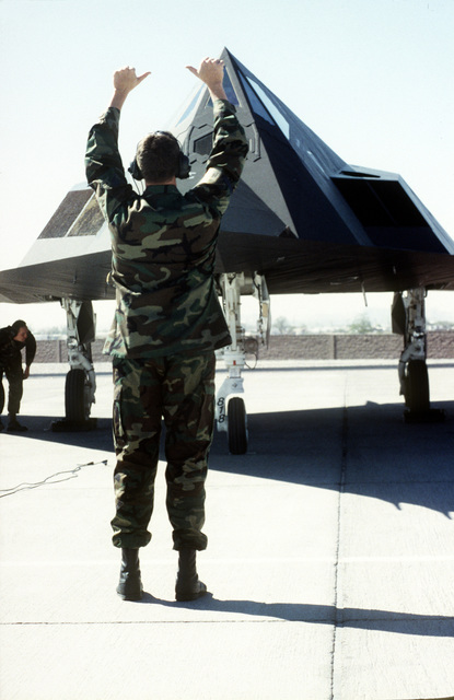 A crew chief signals to the pilot of an F-117A Nighthawk from the 49th Fighter Wing, Holloman Air Force Base, New Mexico as another ground crew member checks the underside of the aircraft during GUNSMOKE 95. Exact Date Shot Unknown