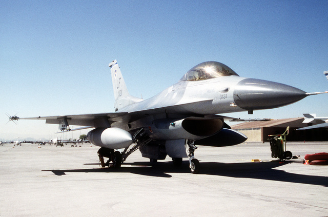 F-16C Falcon from the 310th Fighter Squadron, 56th Fighter Wing, Luke Air Force Base, Arizona, sits on the ramp at the Nevada base awaiting its participation in GUNSMOKE '95. The F-16 has an air combat range data link pod mounted on its left wing tip while an AIM-9 Sidewinder is mounted on the right wing tip. Exact Date Shot Unknown