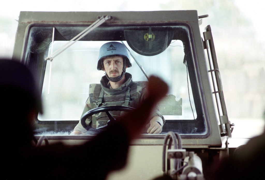 A forward shot of a United Nations ground crew member as he sits in the cab of a forklift. The silhouette of another ground crew member can be seen in the foreground directing the forklift driver. The men are unloading humanitarian relief supplies in Sarajevo. This three-year-old relief effort has been able to resume its missions after a five month hold due to aircraft receiving ground fire over Sarajevo