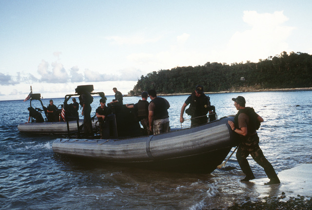CHIEF Gunners Mate (GMGC) Rick Simonsen helps push off two 24-foot rigid hull inflatable boats (RHIB) from Pineros Island Range during exercises with Special Boat Unit Twenty (SBU-20)