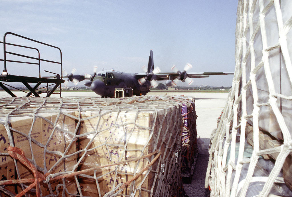 Pallets of humanitarian relief supplies wait at the airport in preparation for loading onto a C-130 Hercules aircraft (in background) which will fly the supplies into Sarajevo, Bosnia-Herzegovina, on relief missions. The three-year-old relief effort has been able to resume its missions after a five month hold due to aircraft receiving ground fire over Sarajevo