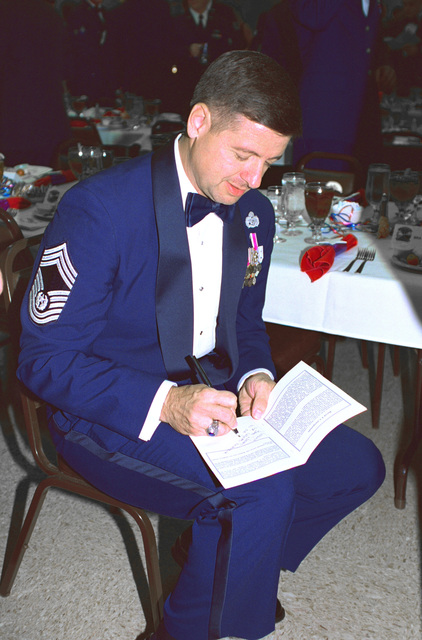CMSAF David J. Campanale sits down and autographs programs during the Dyess AFB Enlisted Dining Out