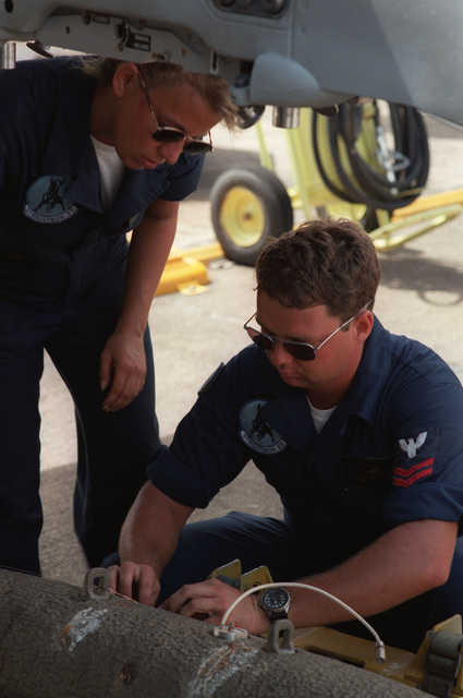 Aviation Ordnanceman Second Class (AO2) Joseph Elliot of Strike Fighter Squadron 37 (VFA-37) instructs AOAN Vonda Dyke on preparation procedures for uploading live Mark 82 cluster bombs to an F/A-18 Hornet aircraft. VFA-37 is assigned to the USS Theodore Roosevelt (CVN-71)