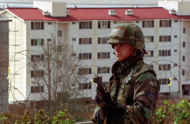 A member of the 607th CBCS (Combat Communication Squadron) deployment force from Camp Humphrey, Republic of Korea, stands ready with his M-16 rifle to defend the outer fence line from aggressors. A large five-story building is in the background