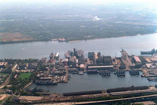 An aerial view of the Philadelphia Naval Shipyard looking south, showing many vessels moored in the Navy Intermediate Ship Maintenance Facility. The shipyard closed on September 30, 1995, but the NISMF will continue to store decommissioned and mothballed ships , The mothballed ships shown here: USS IOWA (BB-61) and WISCONSIN (BB-64); the heavy cruiser DES MOINES (CA-134); the aircraft carriers FORESTALL (CV-59), and SARATOGA (CV-60); two AORs; two AEs; four CGs; two LPDs; and numerous destroyers, guided missile destroyers and frigates
