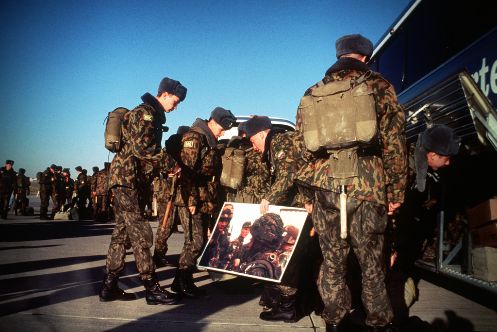 Members of the Russian 27th Guards, Motorized Rifle Division (GMRD) unload their momemtos and MREs, from their visit to the United States off the bus that brought them to the flightline to board the Russian IL-76 transport at McConnell AFB, Kan. The unit participated in Peacekeeper '95