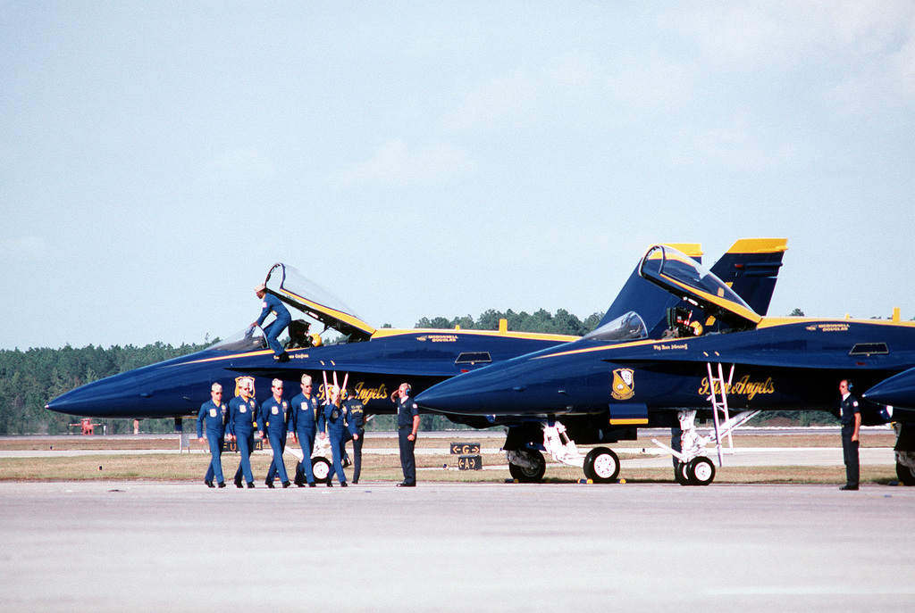 CDR. Donnie Cochran, commanding officer of the Navy's Blue Angel Flight Demonstration Squadron, climbs into the lead F/A-18 Hornet aircraft as the other pilots march off to their waiting planes at the beginning of their portion of the open house airshow at the Naval Air Station