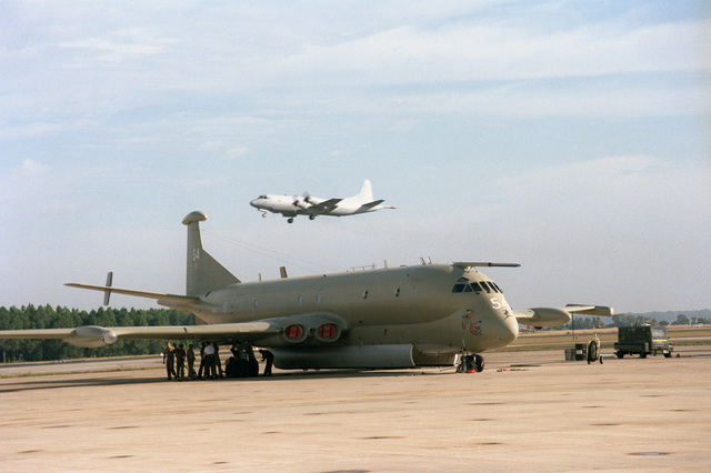 A United Kingdom Royal Navy Nimrod recon and patrol aircraft sits on the tarmac. The 120th CSX Squadron, RAF Kinloss, England maintains a four plane detachment at Jacksonville. In the background, a P-3C Orion aircraft is approaching for landing