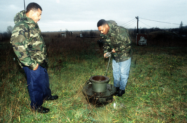 MSGT Willie Mann (right) and SMSGT Robert Morgan, both from the 616th Regional Planning Flight at Aviano AB, Italy, take a fuel sample from one of the large, underground fuel tanks. Fokto, considered a bare base, has been closed for years and the facilities are in poor condition. U.S. military surveyed the condition of four airfields in Hungary for possible use by U.S. Forces should they be sent as a peacekeeping force in Bosnia