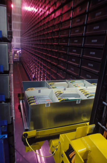 This is an interior view of the Automated Storage and Retrieval System (ASRS) located at the Defense Visual Information Center. Motion media and still media from all the military services are stored here. The ASRS is an environmentally controlled, self-contained, state-of-the-art, robotics track guided system. It is four stories high and about half the size of a football field. This low angle view was taken from the rear of the ASRS with the camera mounted on the robot arm. A bar-coded bin full of motion picture film is ready to be driven forward