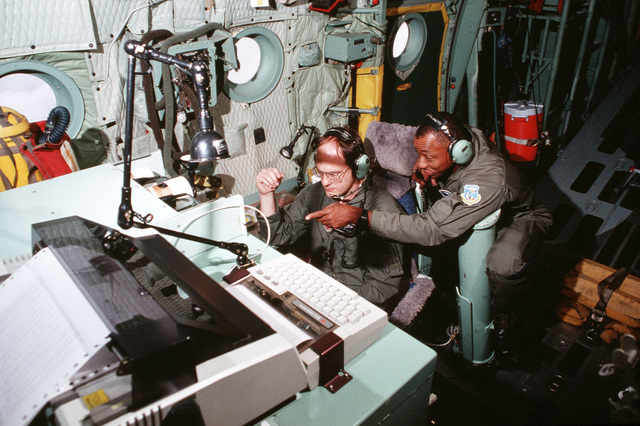 """US Air Force MASTER Sergeant Robert Perry and Technical Sergeant Tony Hlavac (seated) assigned to the 53rd Weather Reconnaissance Squadron, Keesler AFB, Mississippi monitor data from a parachuting weather sensor from inside a USAF WC-130 Hercules aircraft while flying inside the eye of Hurricane Opal. From AIRMAN Magazine December 1995 article """"Hunting Season"""""""