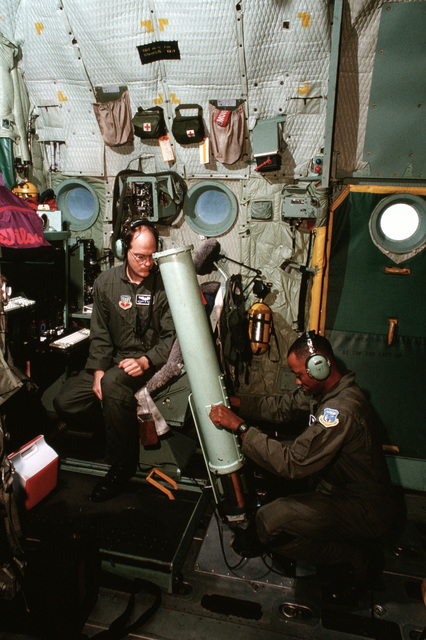 """US Air Force MASTER Sergeant Robert Perry loads a dropsonde sensor into a spring-loaded gun, inside a USAF WC-130 Hercules aircraft as Technical Sergeant Tony Hlavac (seated) watches. Both are assigned to the 53rd Weather Reconnaissance Squadron, (Hurricane Hunters) Keesler AFB, Mississippi. From AIRMAN Magazine December 1995 article """"Hunting Season"""""""