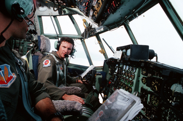 """USAF Captain Brian K. LeTourneau, Commander and pilot and First Lieutenant Scott J. Spitzer sit at the controls of their WC-130 Hercules aircraft from the 53rd Weather Reconnaissance Squadron, (Hurricane Hunters) Keesler AFB, Mississippi while flying a weather reconnaissance mission inside the eye of Hurricane Opal. From AIRMAN Magazine December 1995 article """"Hunting Season"""""""