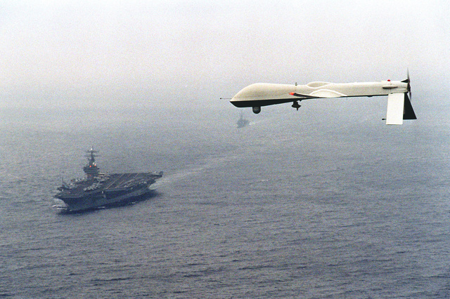 "Left side view of the Predator Unmanned Aerial Vehicle (UAV) as it passes near the nuclear-powered aircraft carrier USS CARL VINSON (CVN-70) during a simulated Navy reconnaissance flight headed by Command Carrier Group One (CVG-1) providing ""near real-time"" infrared and color video images of the ship during the flight"
