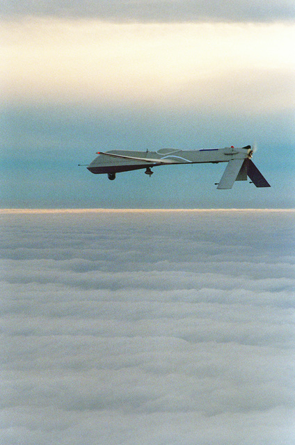 Left rear view of the Navy's Predator Unmanned Aerial Vehicle (UAV) in-flight near San Nicholas Island on a simulated Navy reconnaissance mission. The Predator has a wingspan of 48.4 feet, a length of 26.7 feet and weighs approximately 1,500 pounds when fully fueled. Average speed is approximately 70 knots with a flight endurance of nearly 50 non-stop hours. The aircraft cost is about 3.2 million dollars and is operated by a joint service detachment