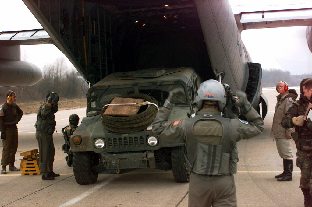 TSGT Mark Hill, the air field manager of the 4100 group provisional, off loads a High-Mobility Multipurpose Wheeled Vehicle (HMMWV) that is marshaled by a load crew member from the 37 Airlift Wing, Ramstein AB Germany. TSGT Hill is in control of all aircraft on the ground and where all vehicles and pallets will be stored during the off loads at Tuzla. The 4100 Group Provisional is in Tuzla to set up airfield operations and bring the air head up to 24 hour capability. The air base will be a major hub of incoming people and supplies in support of the American participation in the Bosnia and Herzegovina