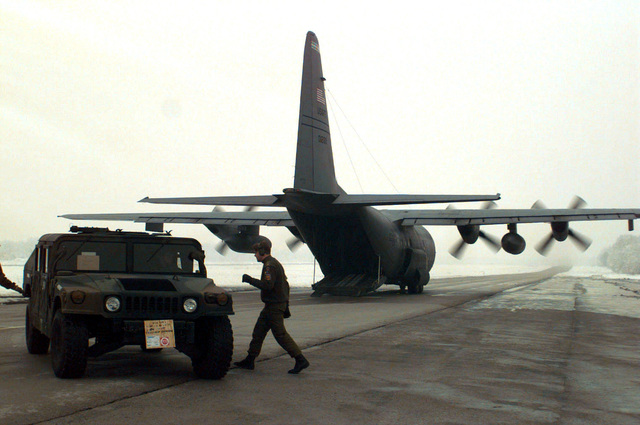 A High Mobility Multi- wheeled Vehicle (HUMMV) is offloaded from the cargo bay of a C-130 Hercules at Tuzla Air Base, Bosnia-Herzegovina