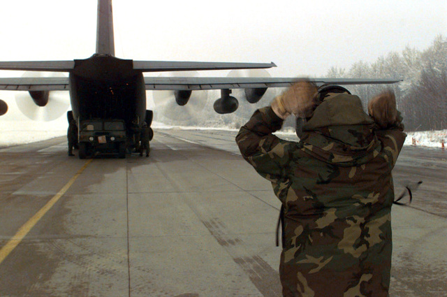 A U.S. Air Force Aerial Port member deployed to Tuzla AB, Bosnia-Herzegovina marshals a High Mobility Multi- wheel Vehicle (HUMMV) from the cargo bay of a C-130 Hercules. The HUMMV will be used to support Operation Joint Endeavor