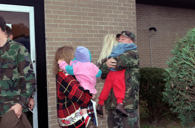 SENIOR AIRMAN William Slaybaugh gives his daughter a hug while saying goodbye to his family prior to boarding a bus to travel to his departure aircraft on the Green Ramp at Pope AFB, N.C. SENIOR AIRMAN Slaybaugh, a member of the 23rd Aeromedical Evacuation Squadron at Pope is deploying to Ramstein Air Base, Germany and then to Tuzla Air Base, Bosnia to establish a Mobile Aeromedical Staging Facility (MASF) in support of Operation Joint Endeavor