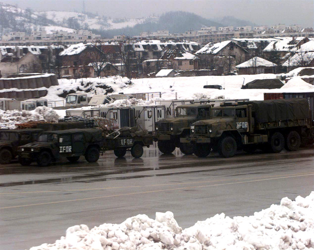 Vehicles assigned to Implementation Forces (IFOR) await to be moved out of Sarajevo, Bosnia-Herzegovina to be used by troops in support of Operation Joint Endeavor. War damaged buildings are in the background
