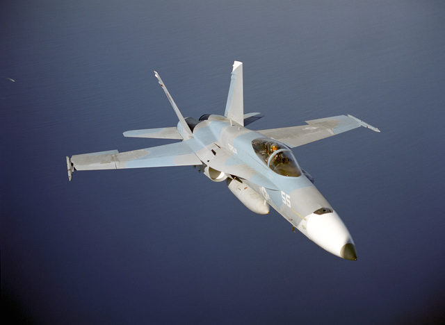 An aerial of F/A-18 Hornet from the TOPGUN school over water