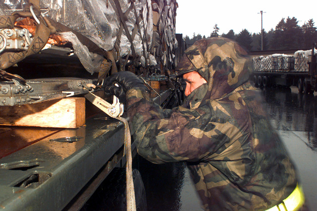 SENIOR AIRMAN John Gonzales, 86th Transportation Squadron, Ramstein AB, Germany, secures a pallet to a flatbed truck before it heads to Tuzla AB, Bosnia-Herzegovina in support of Operation Joint Endeavor