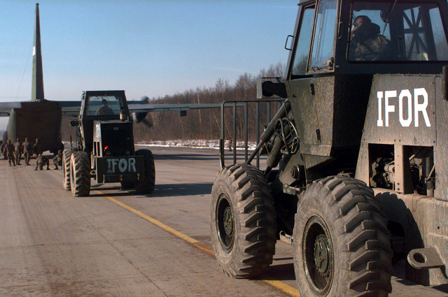 Implementation Force (IFOR) forklifts at Tuzla AB, Bosnia-Herzegovina line up to quickly download vital cargo from arriving C-130's. The C-130's are airlifting supplies in support of Operation Joint Endeavor