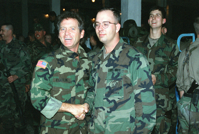 A Navy Seabee of Naval Mobile Construction Battalion One-Thirty-Three (NMCB-133) shakes hands with country music singer Larry Gatlin during a special Christmas Day visit . He performed for the Seabees at a former Russian Army base scud missile magazine now converted to a 200-man bunk room in support of Operation Joint Endeavor, a peace keeping mission to Croatia