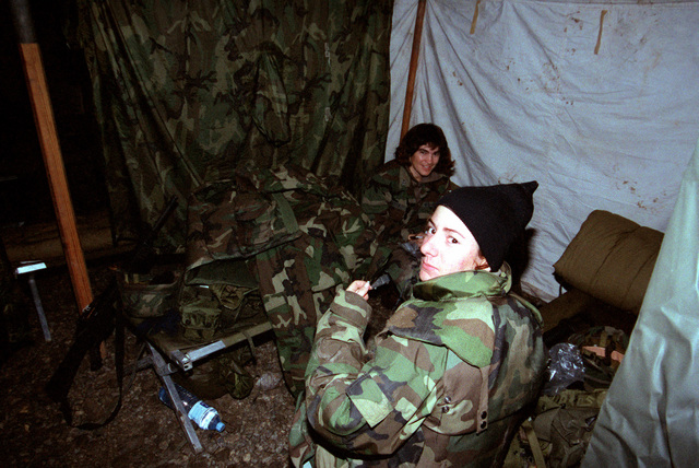 Builder Constructionman Recruit (BUCR) Cristina Laconiz (foreground) and Builder Second Class (BU2) Sandra Grasso eat Meals Ready to Eat (MRE) at the S. A. Hamon Seabee Base Camp. The Seabees build the camp in support of Operation Joint Endeavor, a peace keeping mission to Croatia