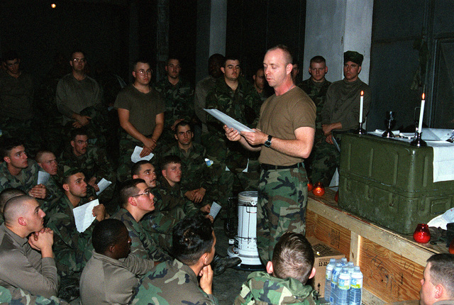 On Christmas Eve, a Navy chaplain holds a special candle-light service for the Seabees of Naval Mobile Construction Battalion One-Thirty-Three (NMCB-133) at a former Russian Army base Scud missile magazine now converted to a 200-man bunk room in support of Operation Joint Endeavor, a peace keeping mission to Croatia