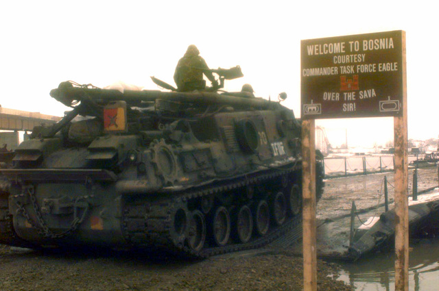 An M88A1 Tank Recovery Vehicle of the First Armored Division and its troops are the first to cross the bridge over the Sava River which links Croatia to Bosnia-Herzegovina. The bridge was constructed in support of Operation Joint Endeavor