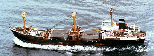A port side view of the Russian Navy Pacific Fleet Yuniy Partizan class cargo ship UFA underway with a commercial deck cargo of steel pipe and commercial vehicles