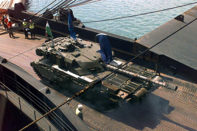 A Royal Army (British) Challenger 1 Main Battle Tank (MBT), the command tank of the 1ST Queen's Dragoon Guards (The Welsh Cavalry), with IFOR markings drives forward on the loading ramp of the VLADIMIR VASLYAEV, a Russian Commercial RO-RO Container (Gearless) ship, onto the dock at the harbor in Split, Croatia, during Operation Joint Endeavor. Operation Joint Endeavor is a peacekeeping effort by a multinational Implementation Force (IFOR), comprised of NATO and non-NATO military forces, deployed to Bosnia in support of the Dayton Peace Accords. (Exact Date Shot Unknown)