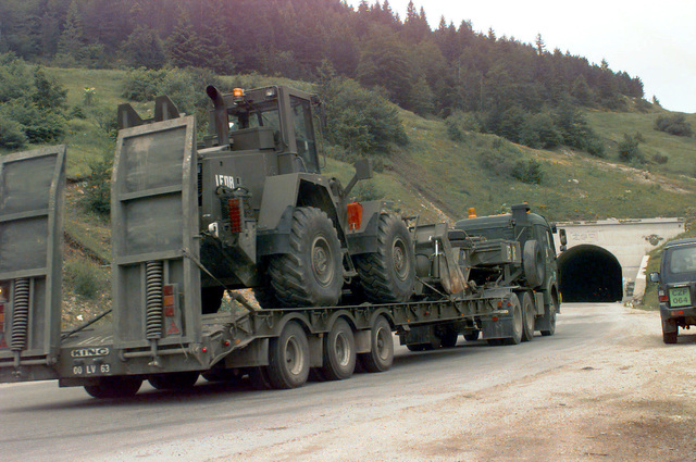 A Royal Army (British) King 35 tonne Tank Transporter Stepframe Semi-trailer unit, carrying a Case 721 Wheeled Loader with IFOR markings, travels along a road in Bosnia-Herzegovina during their deployment in support Operation Joint Endeavor. Operation Joint Endeavor is a peacekeeping effort by a multinational Implementation Force (IFOR), comprised of NATO and non-NATO military forces, deployed to Bosnia in support of the Dayton Peace Accords
