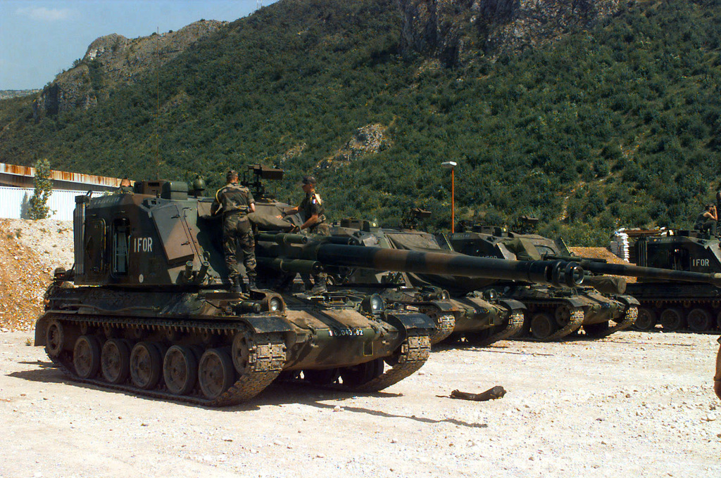 Four French Army Giat 155mm GCT (155mm AUF1) Self-propelled Guns, 40th Regiment d' Artillerie, with IFOR markings are parked at Hekon base, near Mostar, Bosnia-Herzegovina, in support of Operation Joint Endeavor. Two crewmembers are rolled up a canvas covering while standing on the body of vehicle in the foreground, and one crewmember is seated on the fourth vehicle's turret. Operation Joint Endeavor is a peacekeeping effort by a multinational Implemention force (IFOR), comprised of NATO and non-NATO military forces, deployed to Bosnia in support of the Dayton Peace Accords