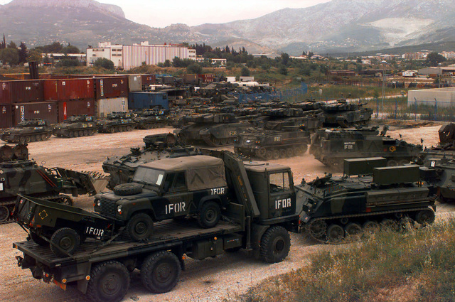 Several Royal Army (British) vehicles, many with IFOR markings, are parked in a staging area. In the foreground are an AWD Bedford TM 6-6 (6x6) 14000 KG Truck, carrying a Land Rover Defender 90 (4x4) Light Vehicle and a Scottorn Military L (510/760kg) Cargo Trailer, and a GKN Defence (Defense) FV432 Armoured (Armored) Personnel Carrier (APC). In the background are Alvis Scorpion Combat Vehicles Reconnaissance, Chieftain Main Battle Tanks, and other armored vehicles. The British are in Croatia to participate in Operation Joint Endeavor, which is a peacekeeping effort by a multinational Implementation Force (IFOR), comprised of NATO and non-NATO military forces, deployed to Bosnia in...