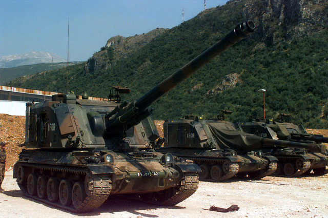 Three French Army Giat (155mm AUF1) Self-propelled Guns, 40th Regiment d' Artillerie, with IFOR markings are parked at Hekon base, near Mostar, Bosnia-Herzegovina, in support of Operation Joint Endeavor. One crewmember is standing on the ground looking at the vehicle in the foreground. Operation Joint Endeavor is a peacekeeping effort by a multinational Implementation Force (IFOR), comprised of NATO and non-NATO military forces, deployed to Bosnia in support of the Dayton Peace Accords