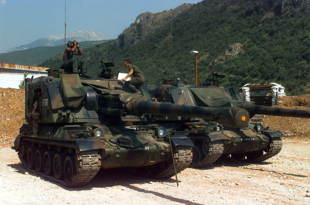 Two French Army Giat 155mm GCT (155mm AUF1) Self-propelled Guns, 40th Regiment d' Artillerie, with IFOR markings are parked at Hekon base, near Mostar, Bosnia-Herzegovina, in support of Operation Joint Endeavor. Three crewmembers are seated or standing on the turret of the vehicle in the foreground and one crewmember is inspecting the vehicle in the background. Operation Joint Endeavor is a peacekeeping effort by a multinational Implemention force (IFOR), comprised of NATO and non-NATO military forces, deployed to Bosnia in support of the Dayton Peace Accords