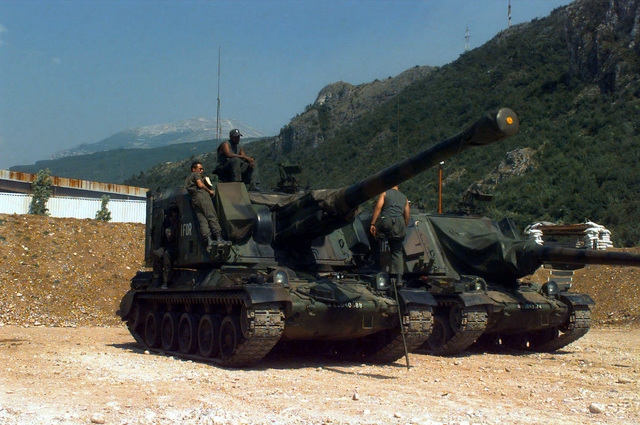 Two French Army Giat 155mm GCT (155mm AUF1) Self-propelled Guns, 40th Regiment d' Artillerie, with IFOR markings are parked at Hekon Base, near Mostar, Bosnia-Herzegovina, in support of Operation Joint Endeavor. Four crewmembers are either seated or standing on or around the turret of the vehicle in the foreground. Operation Joint Endeavor is a peacekeeping effort by a multinational Implemention force (IFOR), comprised of NATO and non-NATO military forces, deployed to Bosnia in support of the Dayton Peace Accords