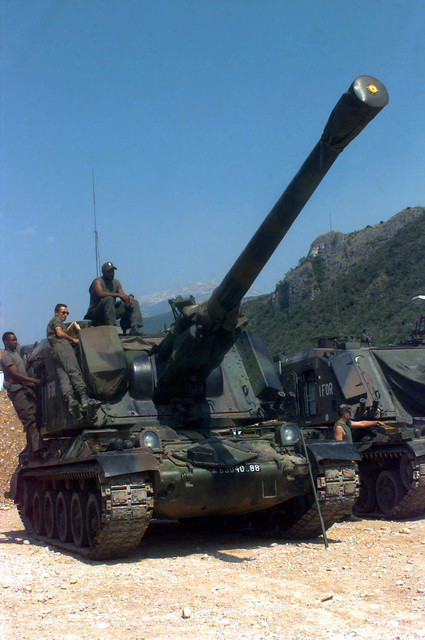 Two French Army Giat 155mm GCT (155mm AUF1) Self-propelled Guns, 40th Regiment d' Artillerie, with IFOR markings are parked at Hekon Base, near Mostar, Bosnia-Herzegovina, in support of Operation Joint Endeavor. Three crewmembers are seated or standing on or around the turret of the vehicle in the foreground and one crewmember is inspecting the vehicle in the background. Operation Joint Endeavor is a peacekeeping effort by a multinational Implemention force (IFOR), comprised of NATO and non-NATO military forces, deployed to Bosnia in support of the Dayton Peace Accords