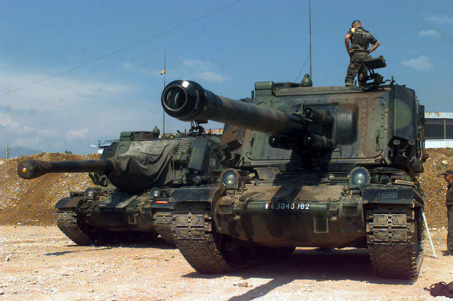 Two French Army Giat 155mm GCT (155mm AUF1) Self-propelled Guns, 40th Regiment d' Artillerie, with IFOR markings are parked at Hekon base, near Mostar, Bosnia-Herzegovina, in support of Operation Joint Endeavor. One crewmember is standing on the turret of the vehicle in the foreground while another crewmember is standing on the ground and looking at the same vehicle. Operation Joint Endeavor is a peacekeeping effort by a multinational Implemention force (IFOR), comprised of NATO and non-NATO military forces, deployed to Bosnia in support of the Dayton Peace Accords
